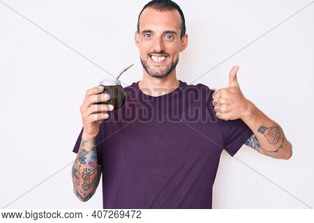 Young handsome man with tattoo drinking mate infusion smiling happy and positive, thumb up doing excellent and approval sign