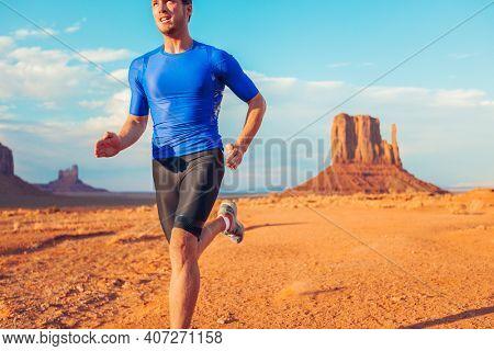 Ultra running competition trail runner man athlete sprinting across desert landscape in Monument Valley, Arizona, USA. Outdoor sport high intensity endurance training.