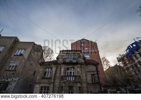 Old, Neglected And Decaying Residential Housing Building Surrounded By Modern Towers, Some Under Con