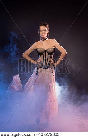 Slim Woman In Corset And Dress In Studio