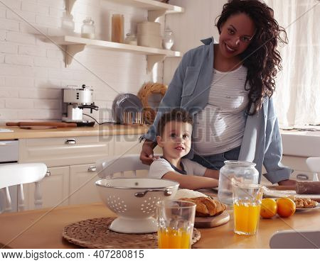 Young Pretty African American Mother With Little Cute Son On Kitchen In Morning Preparing Breakfast,