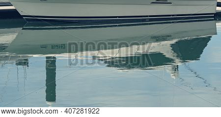 Close Up Of The Sleek Hull Of A Boat On The Waterline Reflected In The Water