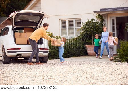 Family Outside New Home On Moving Day Loading Or Unloading Boxes From Car