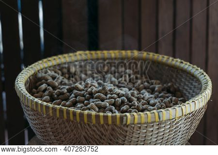 Freshly Steamed Peanuts Sitting In A Woven Basket With Steam Rising Off Of Them. In Front Of A Woode