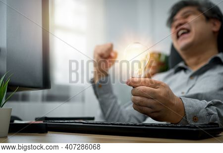 Businessman Holding Lightbulb And Feeling Delighted And Excited By New Innovation And Ideas For Succ
