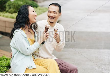 Laughing Happy Young Asian Couple Sitting On Bench, Talking And Eating Icecreams