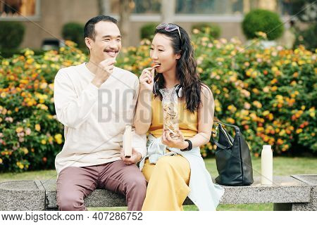 Cheerful Chinese Boyfriend And Girflriend Sitting On Bench, Talking And Eating Delicious Snacks When
