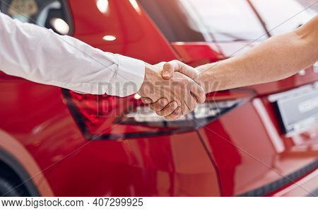 Unrecognizable Male Customer And Manager Shaking Hands Against Red Vehicle In Modern Car Dealership