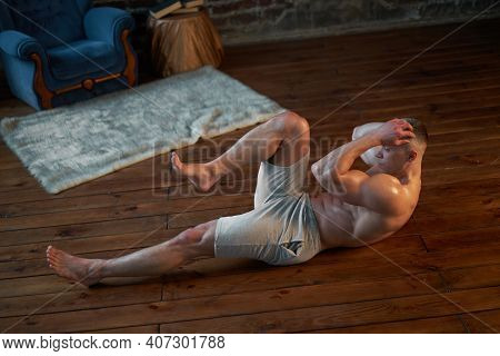 Endurance Workout. Strong Muscular Man Pumps Abdominal Muscles At Home Interior Caucasian Athlete Do
