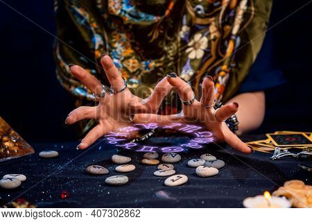 The Female Hands Of The Soothsayer Read The Runes. The Zodiac Circle Glows Above The Runes. Close Up