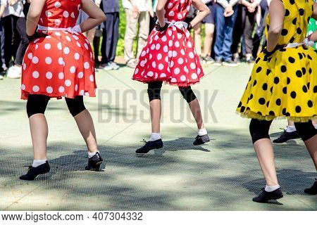 Group Of Girls Dancing In Fashionable Costumes. Dance Group Perform Show In Bright Polka Dots Dresse