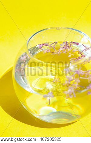 Lilac Flowers Float In The Water. Purple And Pink Flowers In A Glass Vase. On A Yellow  Background