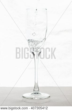 Filling Up The Champagne Glass Water  Isolated On A White Background