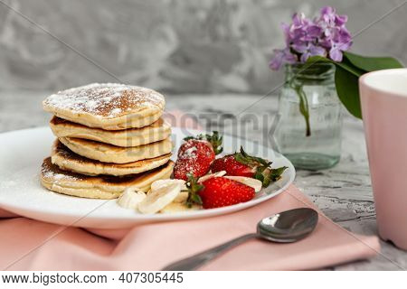 A Stack Of Pancakes With A Pink Tea Mug And  Fresh Strawberries On A White Plate On A Light Backgrou