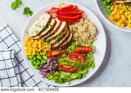 Grilled Chicken Breast With Brown Rice And Vegetables In A White Plate, Gray Background. Healthy Foo