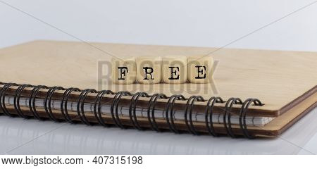 Word Free Made With Letters On Wooden Blocks On The Wooden Notepad