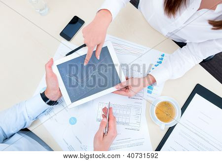 Businessman discussing with financial analyst business development strategy project and using apple ipad with chart on a screen. Top view photoshoot. poster