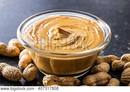 Peanut butter in bowl and peanuts on black table.