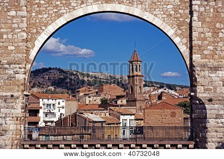 View of the Los Arcos Aqueduct with town buildings to the rear Teruel Teruel Province Aragon Spain Western Europe. poster