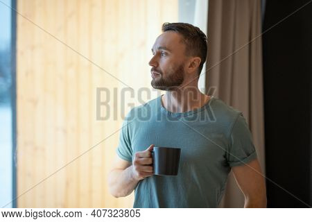 Young bearded relaxed man in grey t-shirt holding mug with hot tea or coffee and looking through large window while staying at home