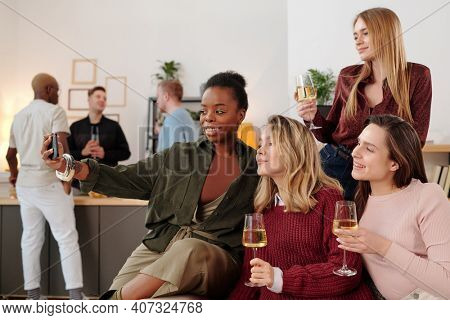 Happy young intercultural women with flutes of champagne making selfie while cheering up and enjoying home party against their boyfriends