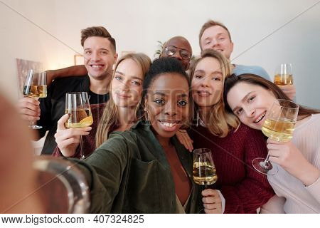 Large group of happy young intercultural friends in smart casualwear making selfie while cheering up with flutes of champagne at party