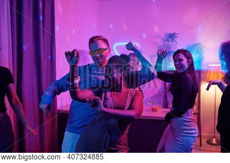 Group of young cheerful intercultural friends in smart casualwear dancing excitedly at home party in living-room illuminated with pink lighting