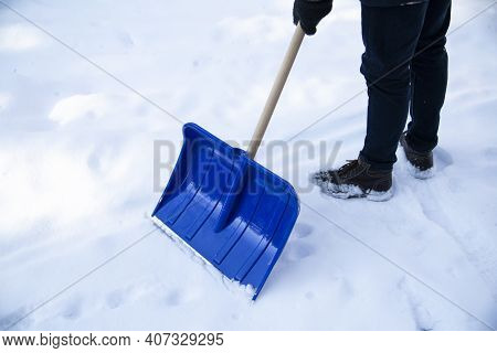 A Blue Snow Shovel During Shoveling Snow From A Sidewalk. Winter Household Chores.