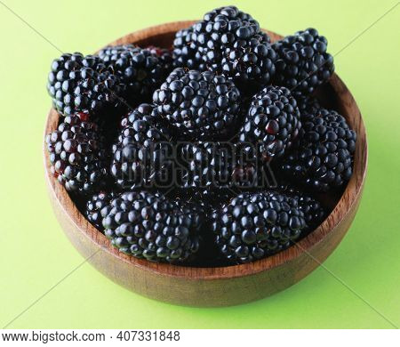 Blackberries in a wooden bowl. Ripe and tasty black berry isolated on green baclground. Close up.
