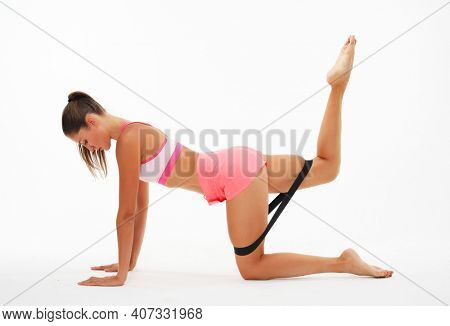 Resistance band fitness. Young woman doing leg workout donkey kick floor exercises with strap elastic. Glute muscle activation with kickback for thighs cellulite. Sport concept.