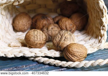 Food Background. Whole Walnut Close-up. A Round Walnut Spilled From A Basket On A Blue Wooden Table.