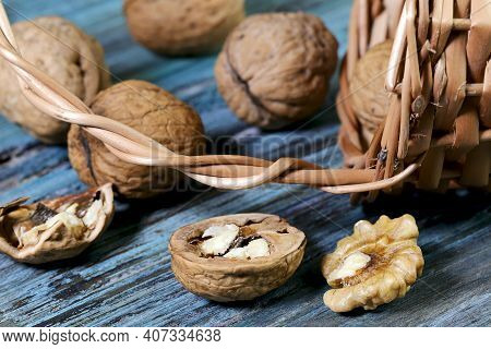 Food Background. Walnut Close-up. A Round Walnut Spilled From A Basket On A Blue Wooden Table.
