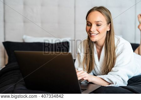 Young Beautiful Woman In Towel And Bathrobe Sitting On Bed At Home And Working On Her Laptop. Beauti