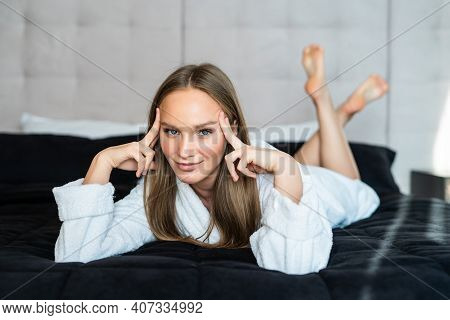 Beautiful Young Woman In Bathrobe Resting On Bed After Shower At Home