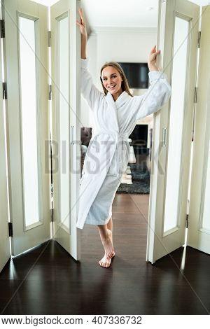 Near Glass Door. Long-legged Sexy Woman Standing Near Glass Door In Living Room After Having Shower