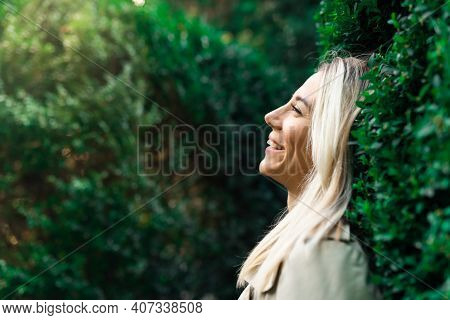Side Portrait Of Blonde Smiling Woman Breathe With Fresh Air In Green Forestor Park In Summer Wearin