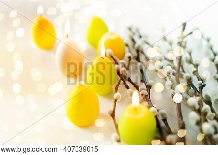 holidays and object concept - pussy willow branches and easter egg candles over bokeh lighs