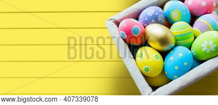 easter, holidays, tradition and object concept - close up of colored easter eggs in basket over yellow wooden boards background