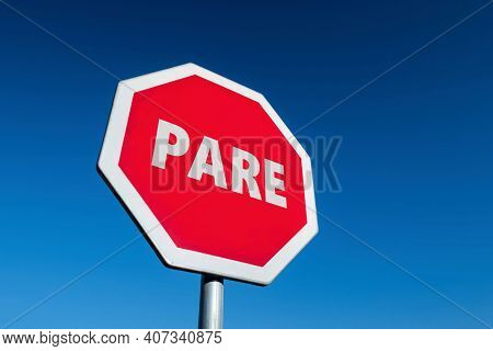 Traffic Sign With The Word Stop Translated To English (pare In Spanish And Portuguese) In Perspectiv