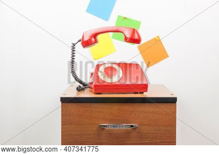 Urgent call waiting , classic red telephone receiver, old telephone on white background, flying in weightlessness with wooden desktop.