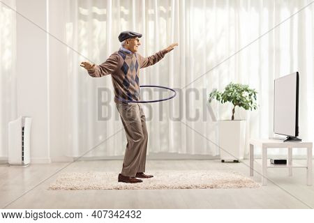 Cheerful man having fun and spinning a hula hoop isolated on white background