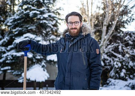 Man In Winter Clothes Holding A Handle Of A Snow Shovel. Shoveling Snow, Winter Household Chores.