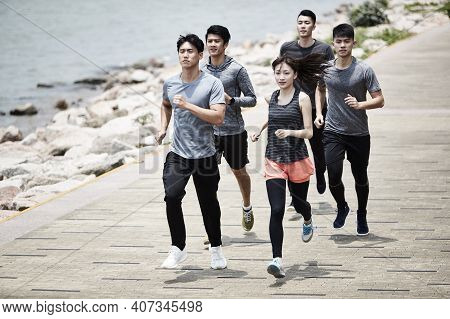 Group Of Five Young Asian Adult Men And Woman Running Training Outdoors