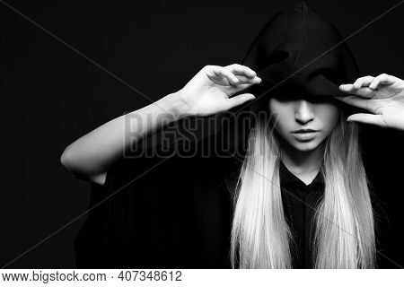 Witch In Mantle On Dark Background, Black And White Effect. Scary Fantasy Character