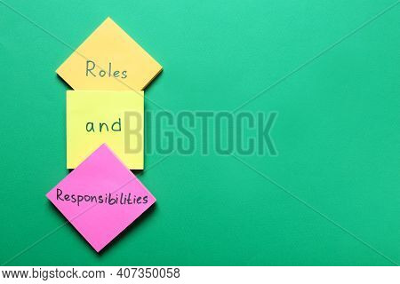 Sticky Notes With Words Forming Phrase Roles And Responsibilities On Green Background, Flat Lay. Spa