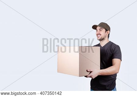 Image Of A Happy Young Delivery Man  With Parcel Post Box Isolated Over White Background. Courier De