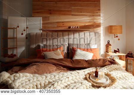 Cozy Bedroom Interior With Knitted Blanket And Cushions