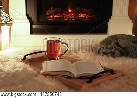 Cup Of Tea And Book On Fuzzy Rug Near Fireplace At Home. Cozy Atmosphere