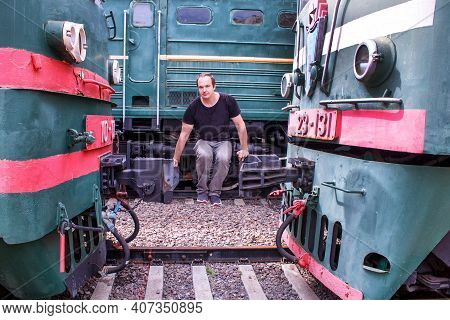 Strength Training On The Railway. Dangerous Journey Outside Of The Train. A Man Between Two Locomoti