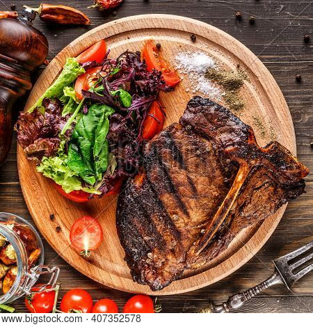 Beef T-bone Steak, Herbs And Spices On A Dark Table. Top View. Free Space For Your Text.